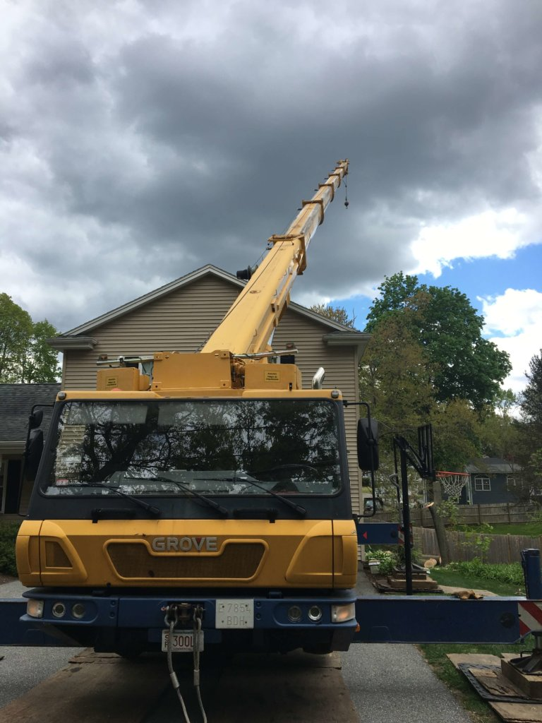 Crane is used in removal of large tree in tight space-Burlington,MA- Middlesex Tree Service